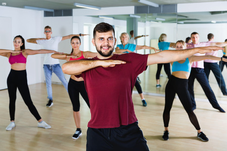 Happy  men women performing modern dance in fitness studio Imagens