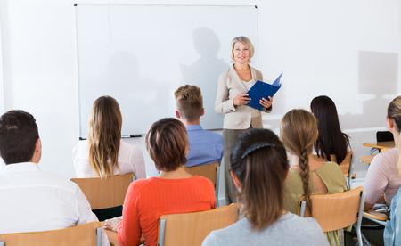 Grupo de estudiantes escuchando atentamente la conferencia de la profesora en el aula Foto de archivo