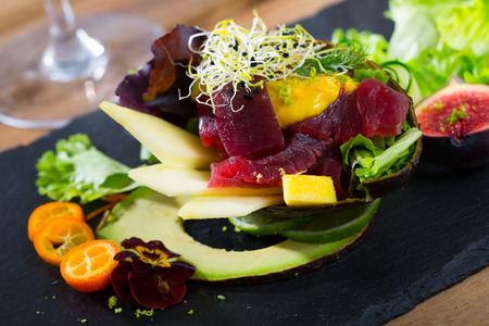 Colorful salad with raw tuna, chopped mango and avocado garnished with cumquat, figs, greens and flowers Imagens - 115706028