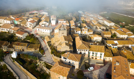 View from drone of roofs of houses in traditional village of Liedena in foggy morning, Navarre, Spain