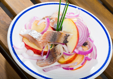 Traditional Norwegian salad of marinated herring fillet, fresh apples and onion rings