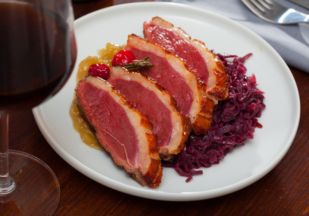 Tasty roasted duck Magret with stewed cabbage, herbs and sauces on plate