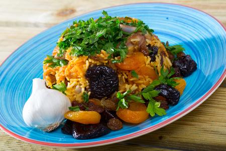 Tasty lamb pilau with dried fruits, raisins, sweet garlic and parsley