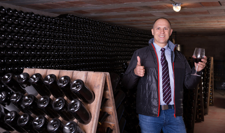 Male winemaker giving tour around winery, inviting to tasting red wine of own production