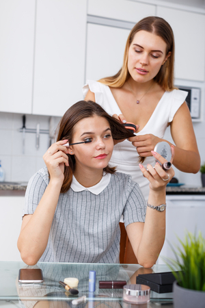 Two modern girls friends having conversation and applying cosmetics in kitchen