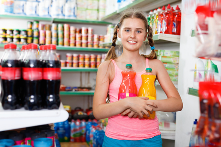 Glad  positive smiling  tween girl choosing and buying food products at grocery shop