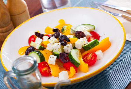 Healthy summer salad with fresh tomatoes, cucumber, bell pepper, feta cheese and olives (Greek salad) seasoned with herbs