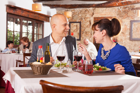 Portrait of glad couple having romantic dinner in restaurant