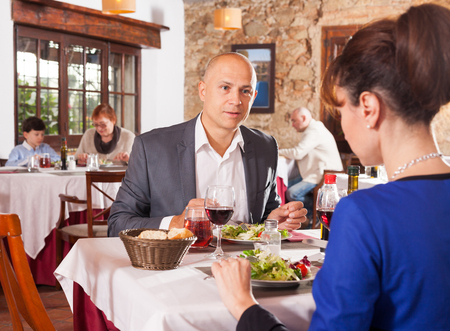 Adult couple at restaurant having dinner and talking