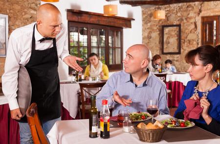 Hombre y mujer indignados descontentos con la calidad de la comida en el restaurante