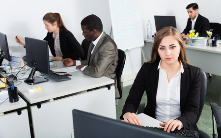 Young cheerful  business woman working with laptop in  workplace with international team