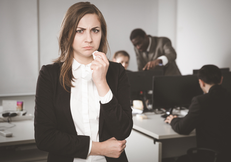 Unhappy businesswoman standing in office on backround with working colleagues