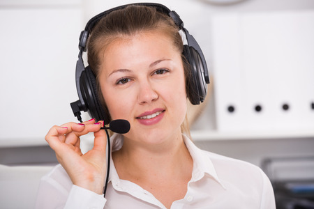 Portrait of operator which is talking with client in the office.