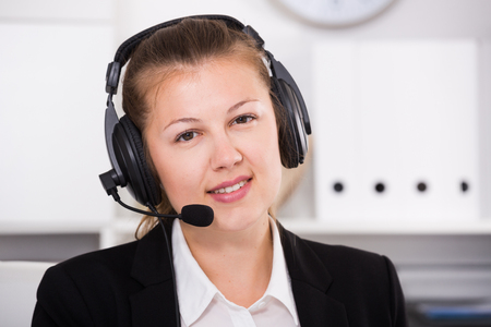 Portrait of young operator female in black suit which is talking by headset with client in the office. Stock Photo