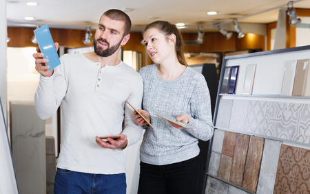 Glad couple looking sample of  ceramic tile  in shop
