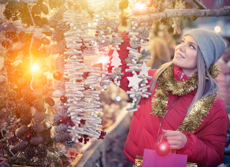 Positive smiling woman at fair near counter with Christmas gifts Stock Photo - 115757206
