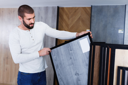 Portrait of young positive  man choosing wood laminated flooring in shop