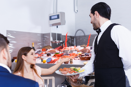Young female talking with waiter in fish restaurant, pointing to icy showcase with seafood Banque d'images