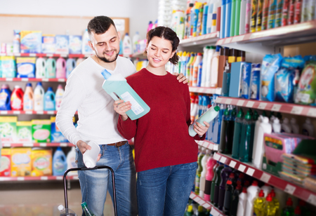 two smiling adult people in good spirits selecting detergents оn the shelves in the store