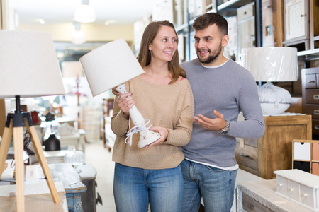 Loving couple looking for stylish table lamp in shop of secondhand furniture Stockfoto