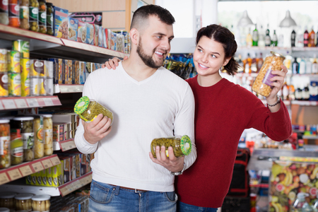 Couple of customers buying tinned food at grocery shop