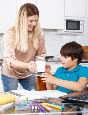 Smiling woman giving lunch to her son doing homework at kitche Imagens - 115902765