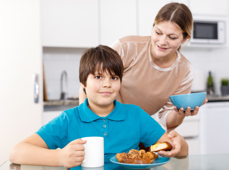 Portrait of happy family of mother and son eating at home kitchen