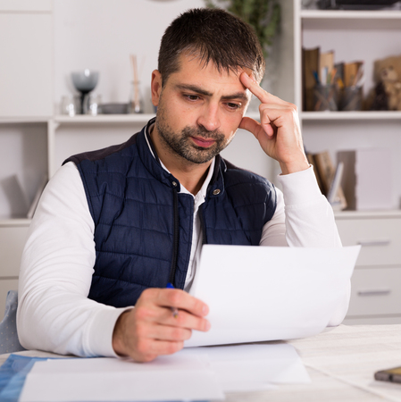 Sadly young man struggling to pay utility bills and home rent