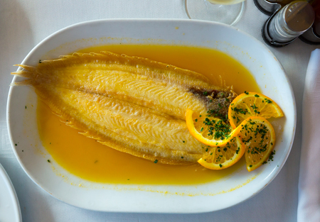 Delicious dover sole cooked in orange sauce served on white plate