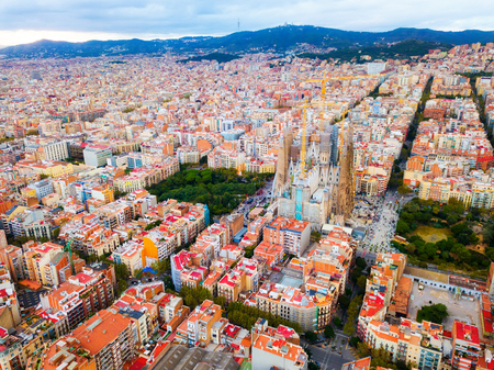 Modern urban landscape in Barcelona, panoramic view from drone of Eixample district and Sagrada Familia