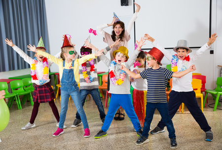Cheerful pupils and female teacher with funny hats and festive accessories posing together in schoolroom Reklamní fotografie