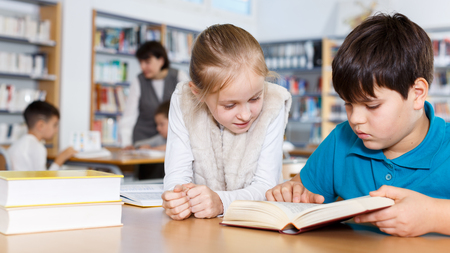 Portrait of two school children preparing for lesson in school library, reading textbooks together