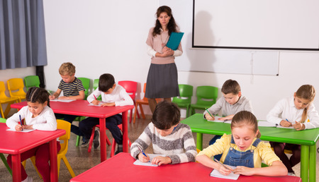 Portrait of focused pupils of elementary school working in classroom with female teacher