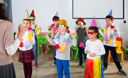 Group of cheerful school kids wearing festive hats having fun with their teacher during celebrating of holiday at school Imagens