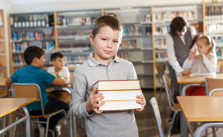 Smiling intelligent boy holding pile of books while standing in modern school library