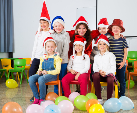 Portrait of young female teacher and happy school children in Santa hats posing together in classroom