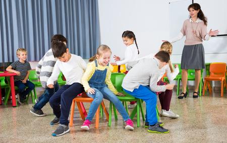Alumnos riendo felices de la escuela primaria que se divierten durante el descanso con su maestro, tocando sillas musicales Foto de archivo