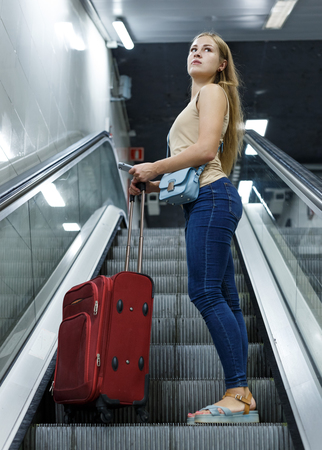 Portrait of young woman traveler on escalator going to subway Фото со стока