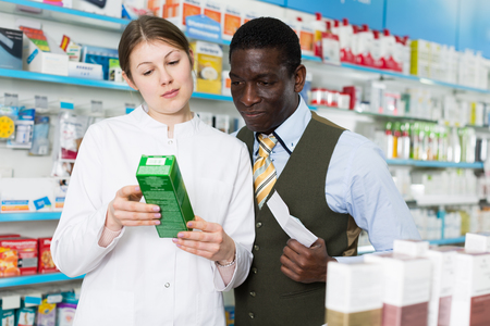 Young woman explaining prescribed medicine to African American man in pharmacy