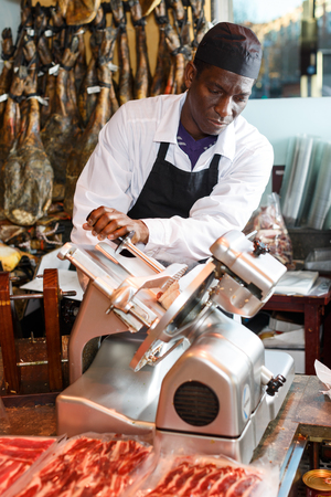 Confident African American seller slicing ham on slicer machine in butcher shop Stock fotó