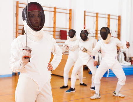 Portrait of sporty young female in mask with foil at fencing workout