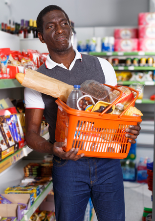 Cheerful African American man with cart shopping in shop