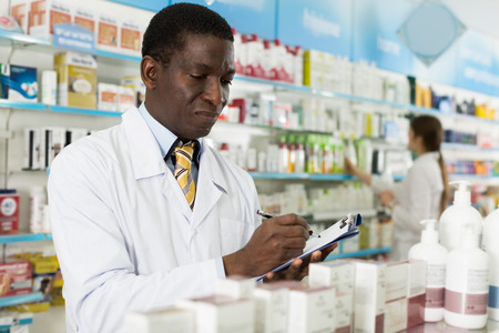 Man  specialist of pharmacy making notes on clipboard during inventory in shop