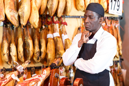 Confident meat delicatessen shop owner posing near counter with traditional Spanish ham