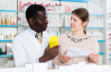 African American man pharmacist discussing prescription medicines with woman customer in pharmacy. Focus on woman