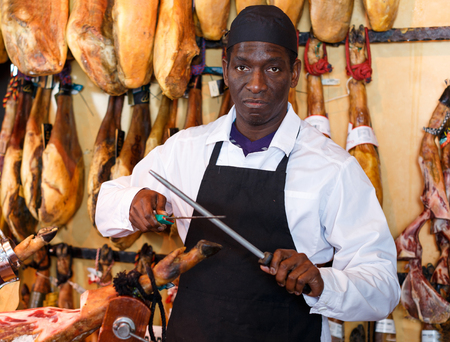 African American male seller sharpening knife in meat store on background of rack with jamon Reklamní fotografie