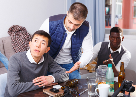 Chagrined young man sitting at home table having problems in relationship with friends