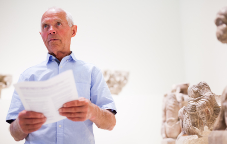 Mature male tourist reading brochure with exhibition program standing near sculptures in historical museum