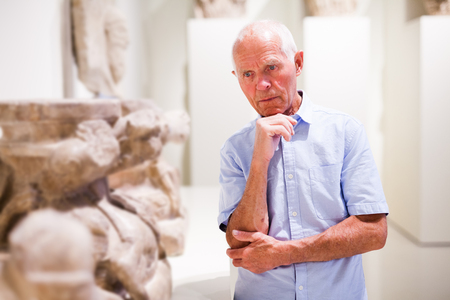Elderly man examining exhibition in museum of ancient sculpture