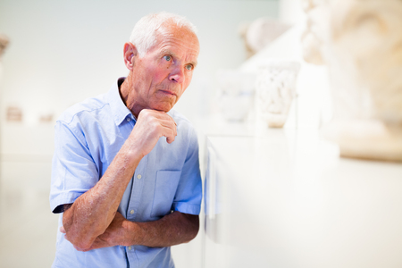 Intelligent aged male tourist visiting sculptures exposition in museum